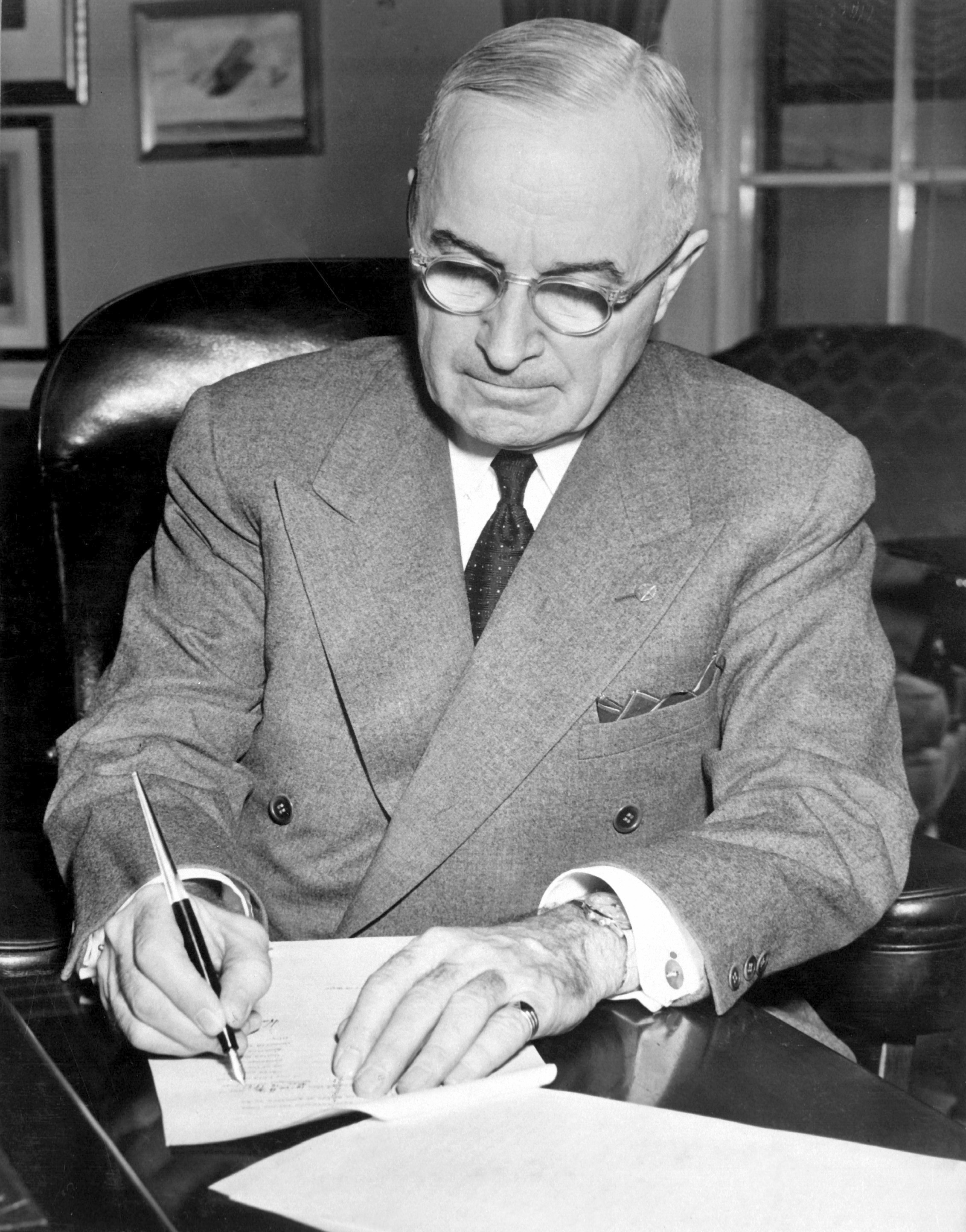 Truman signing document.