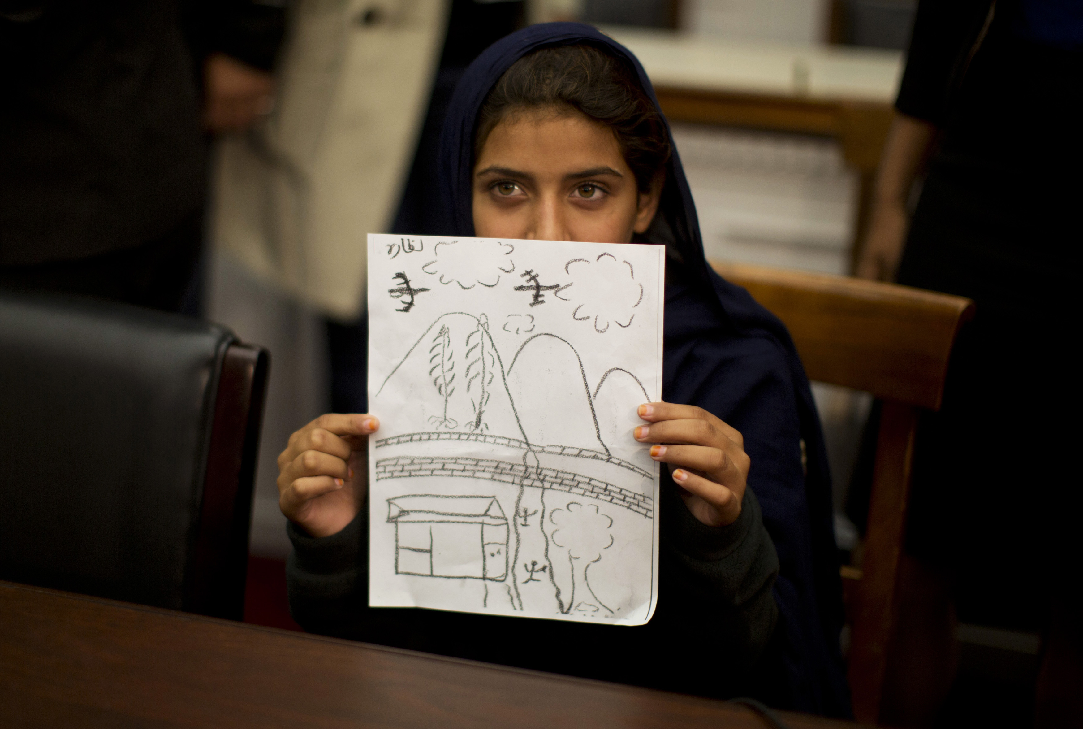 Pakistani girl holds drawing of a drone