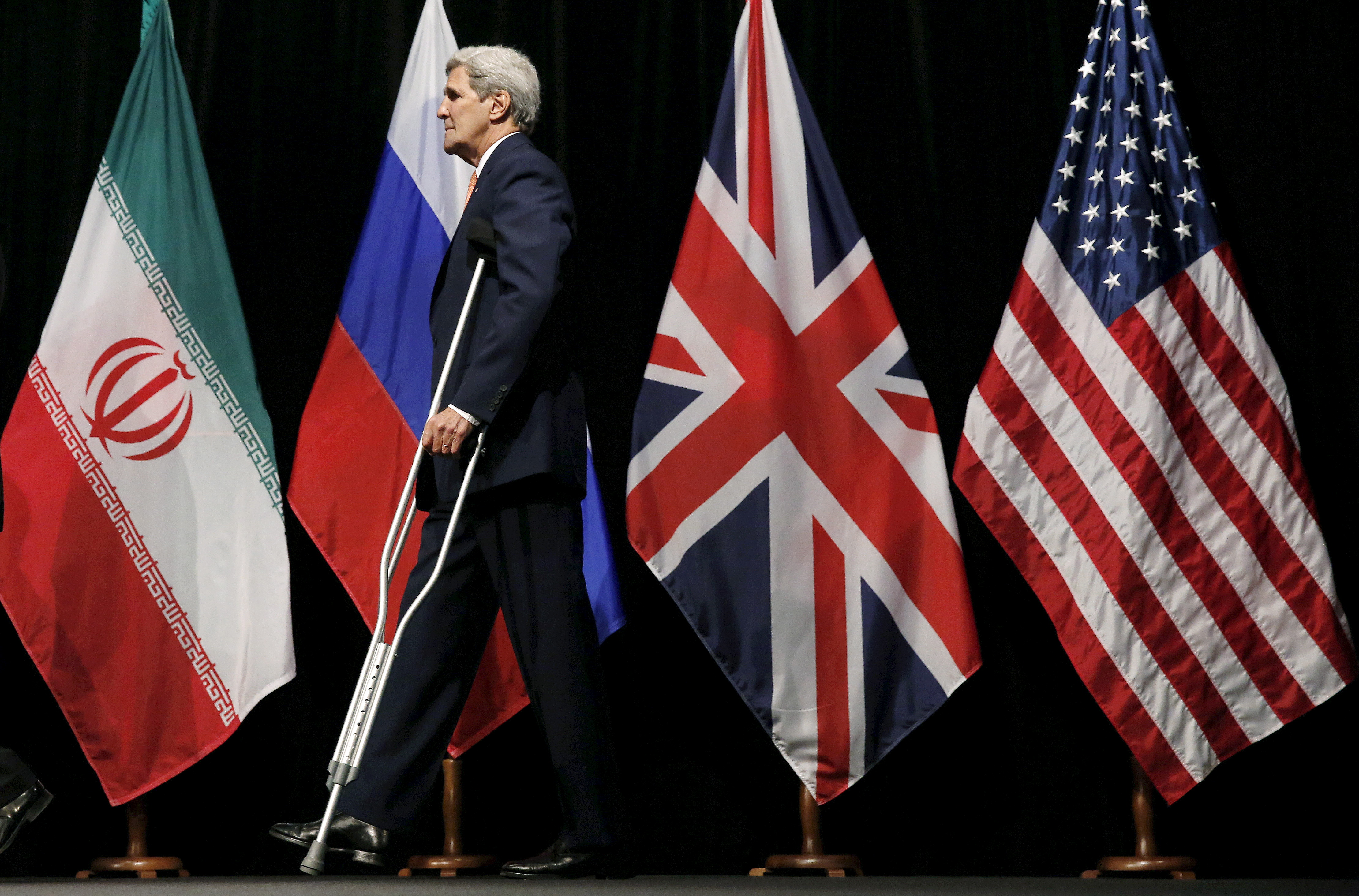 Secretary of State John Kerry walking past flags.