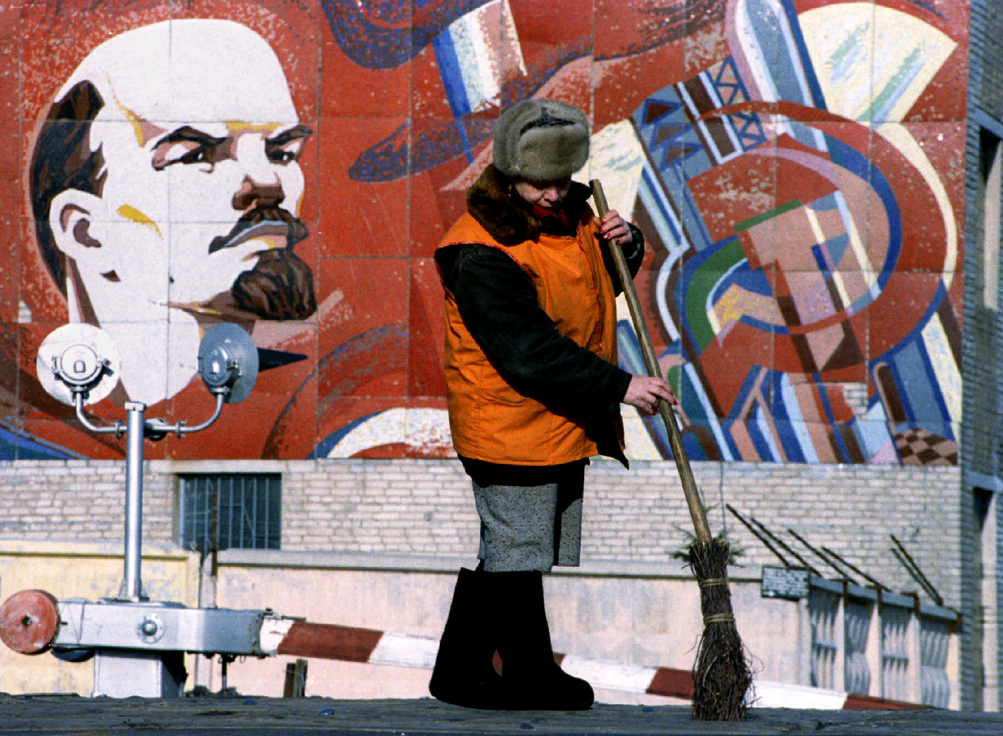 worker in front of a Soviet mural