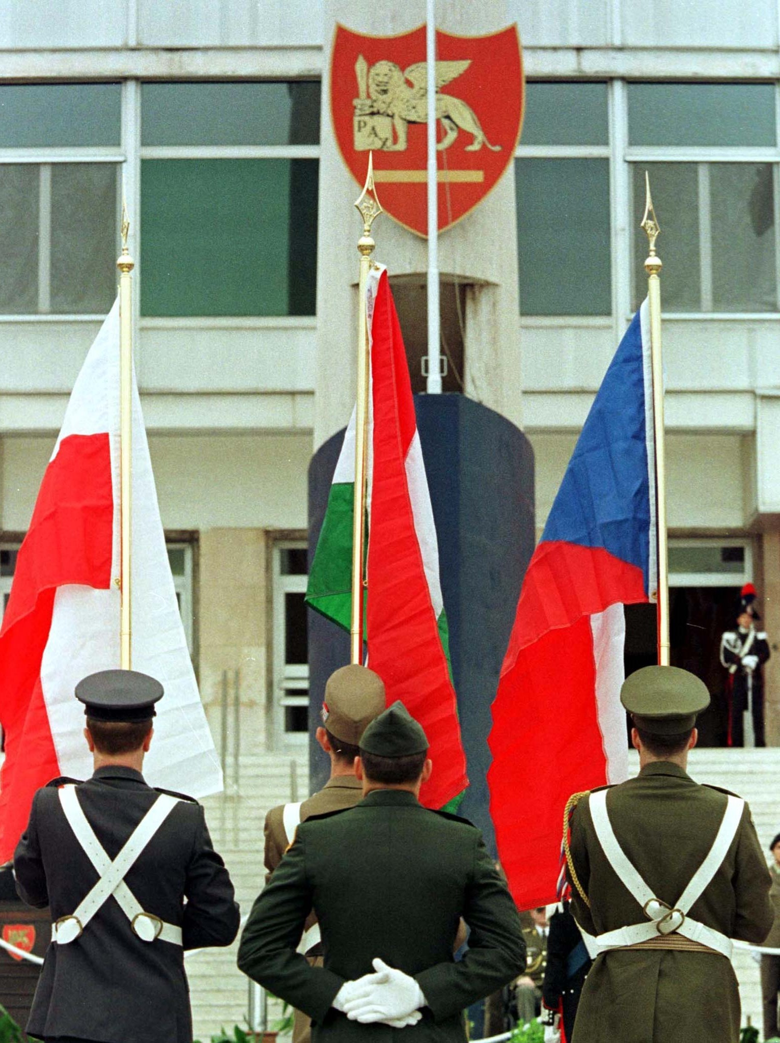 soldiers in front of flags of Eastern Europe
