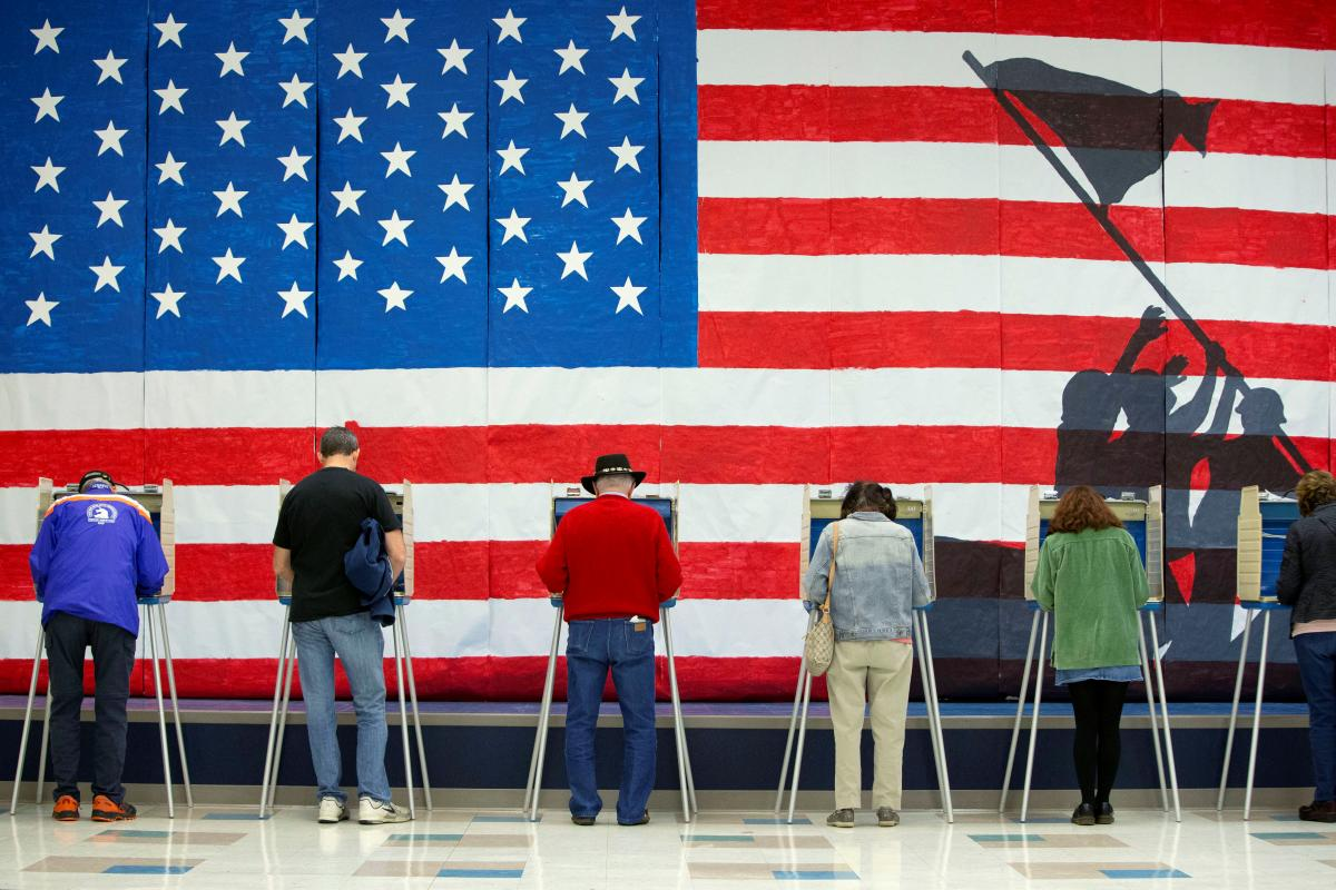 Americans voting in front of a flag