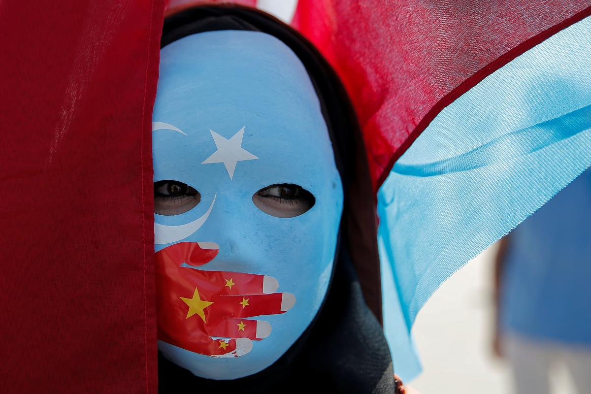 Woman at a protest with a mask on where a red hand is painted over her mouth
