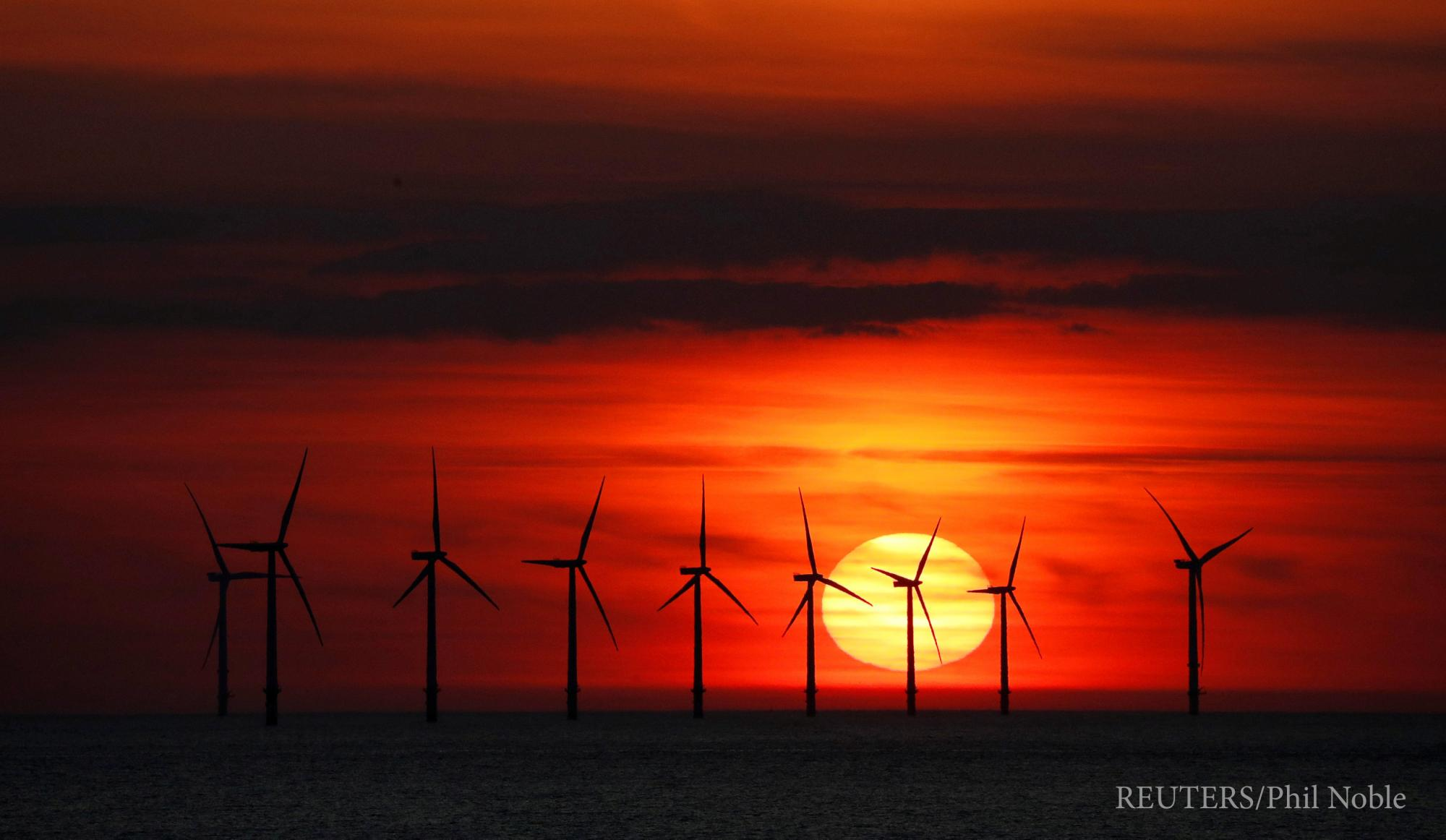 Wind turbines in front of a fiery red sunset
