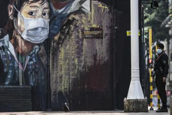 A mural of a girl wearing a mask is on a wall in Colombia with a Colombian guard in a mask next to it