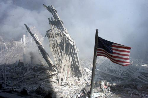 Shards of a burned building sit behind an American flag on September 11, 2001