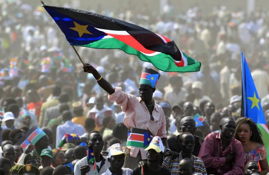 South Sudanese citizen waving a flag.