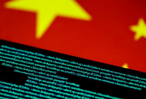 Computer code is seen on a screen above a Chinese flag in this July 12, 2017