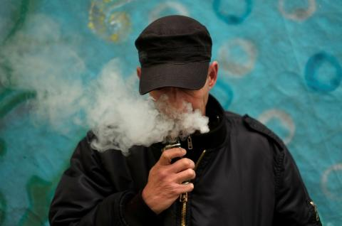 A man poses for a picture, as he vapes at home